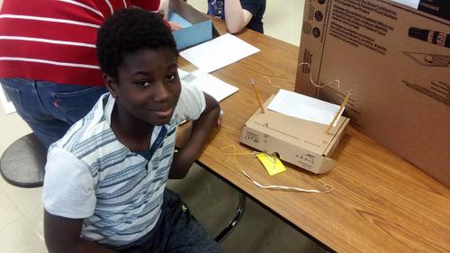 Photo of a young inventor and his project.