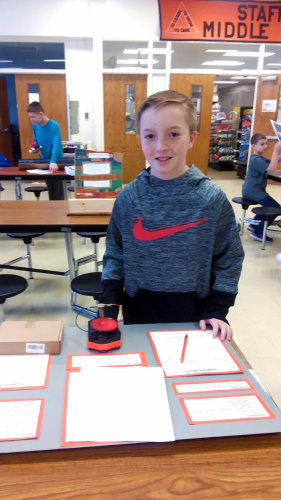A young inventor displays his work.
