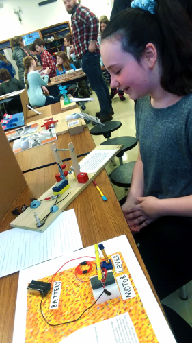 A young inventor displays her work.